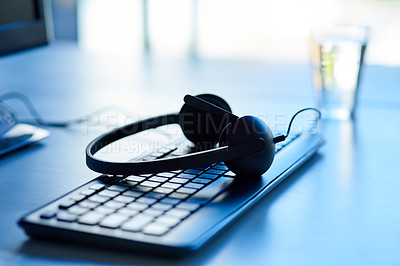 Buy stock photo Closeup shot of a headset lying on a keyboard in an office