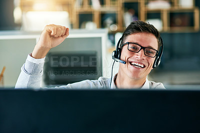 Buy stock photo Portrait of a young call centre agent cheering while working in an office