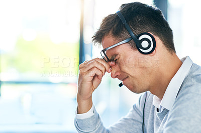 Buy stock photo Shot of a young call centre agent looking stressed out while working in an office