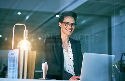 Buy stock photo Portrait of a confident businesswoman working on a laptop in an office at night