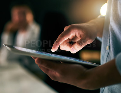 Buy stock photo Closeup shot of an unrecognizable businessman working on a digital tablet in an office at night