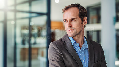 Buy stock photo Shot of a thoughtful young businessman working in a modern office