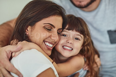 Buy stock photo Portrait of an adorable little girl hugging her mother with her father's arm around them