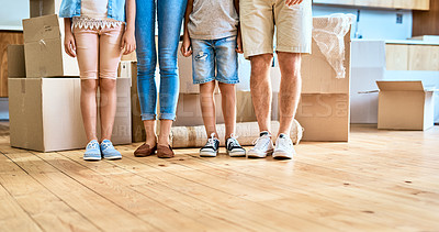 Buy stock photo Low angle shot of a unrecognizable family's bottom half while they stand next to each other at home during the day