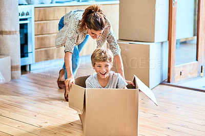 Buy stock photo Shot of a cheerful young woman pushing her son around in a box imagining its a car inside at home during the day