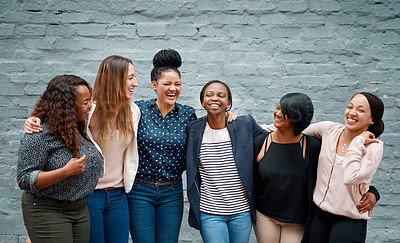 Buy stock photo Portrait of a diverse group of young women standing together against a gray wall outside