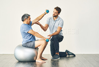 Buy stock photo Full length shot of a young male physiotherapist assisting a senior patient in recovery