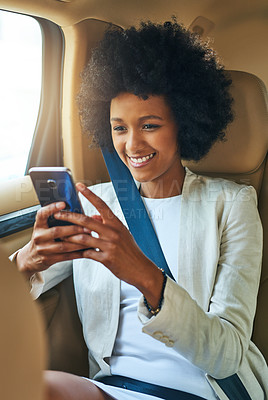 Buy stock photo Shot of a cheerful young businesswoman browsing on her cellphone while being seated in the passenger seat of a car on her way to work