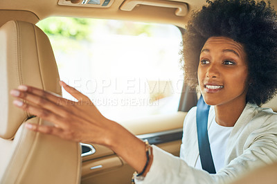 Buy stock photo Shot of a cheerful young businesswoman seated in a passenger seat of a car while giving direction to her work during the day