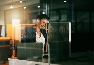 Buy stock photo Shot of a young businesswoman suffering with neck pain while working late in an office