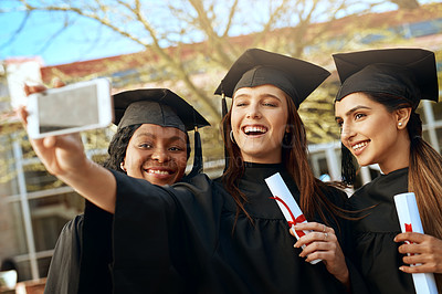 Buy stock photo Shot of a group of young women taking selfies with a mobile phone on graduation day