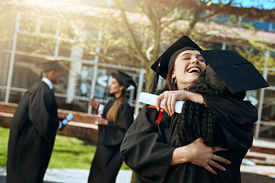 Buy stock photo Shot of two happy young women hugging on graduation day