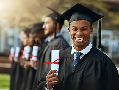Buy stock photo Portrait of a young man holding his diploma while standing with his fellow students on graduation day