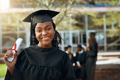 Buy stock photo Portrait of a happy young woman holding a diploma on graduation day