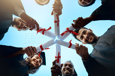 Buy stock photo Low angle shot of a group of students holding their diplomas together on graduation day