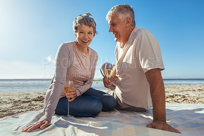 Buy stock photo Shot of a happy mature couple relaxing and having wine together at the beach