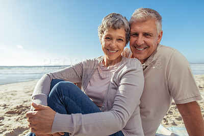 Buy stock photo Shot of a happy mature couple relaxing together at the beach