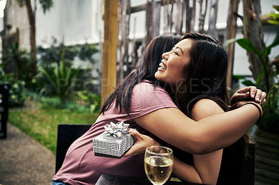 Buy stock photo Cropped shot of two female friends embracing each other at a restaurant outside