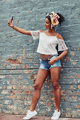 Buy stock photo Shot of an attractive  young woman taking a selfie against a brick wall outside