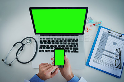 Buy stock photo High angle shot of an unrecognizable doctor using a laptop and cellphone with a green screen in his office