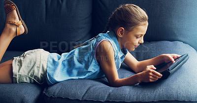 Buy stock photo Shot of a cute little girl using a digital tablet on the sofa at home