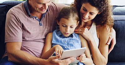 Buy stock photo Shot of a cute little girl using a digital tablet with her mother and father on the sofa at home