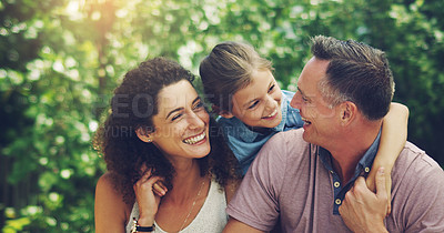Buy stock photo Shot of an affectionate little girl spending quality time with her mother and father outdoors