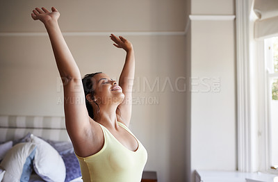 Buy stock photo Shot of a beautiful young woman waking up and stretching in her bedroom at home