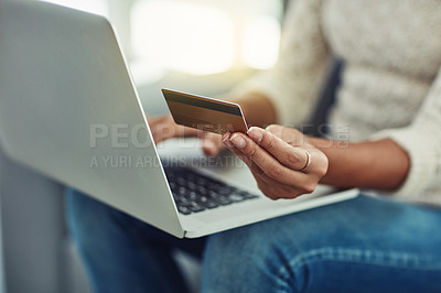 Buy stock photo Shot of an unrecognizable woman making payments online with a credit card at home