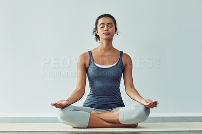 Buy stock photo Studio shot of an attractive young woman practicing yoga against a grey background