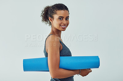 Buy stock photo Studio shot of an attractive young woman getting ready to practice yoga against a grey background