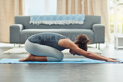 Buy stock photo Shot of an attractive young woman practicing yoga at home