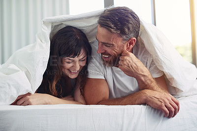 Buy stock photo Shot of a cheerful young couple crawling out of bed while having a laugh together during morning hours