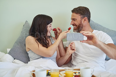 Buy stock photo Shot of a cheerful young couple sitting in bed while enjoying breakfast together and taking a selfie during morning hours