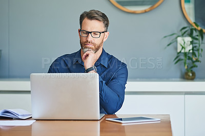 Buy stock photo Shot of a focussed middle aged man working on his laptop while contemplating at home during the day