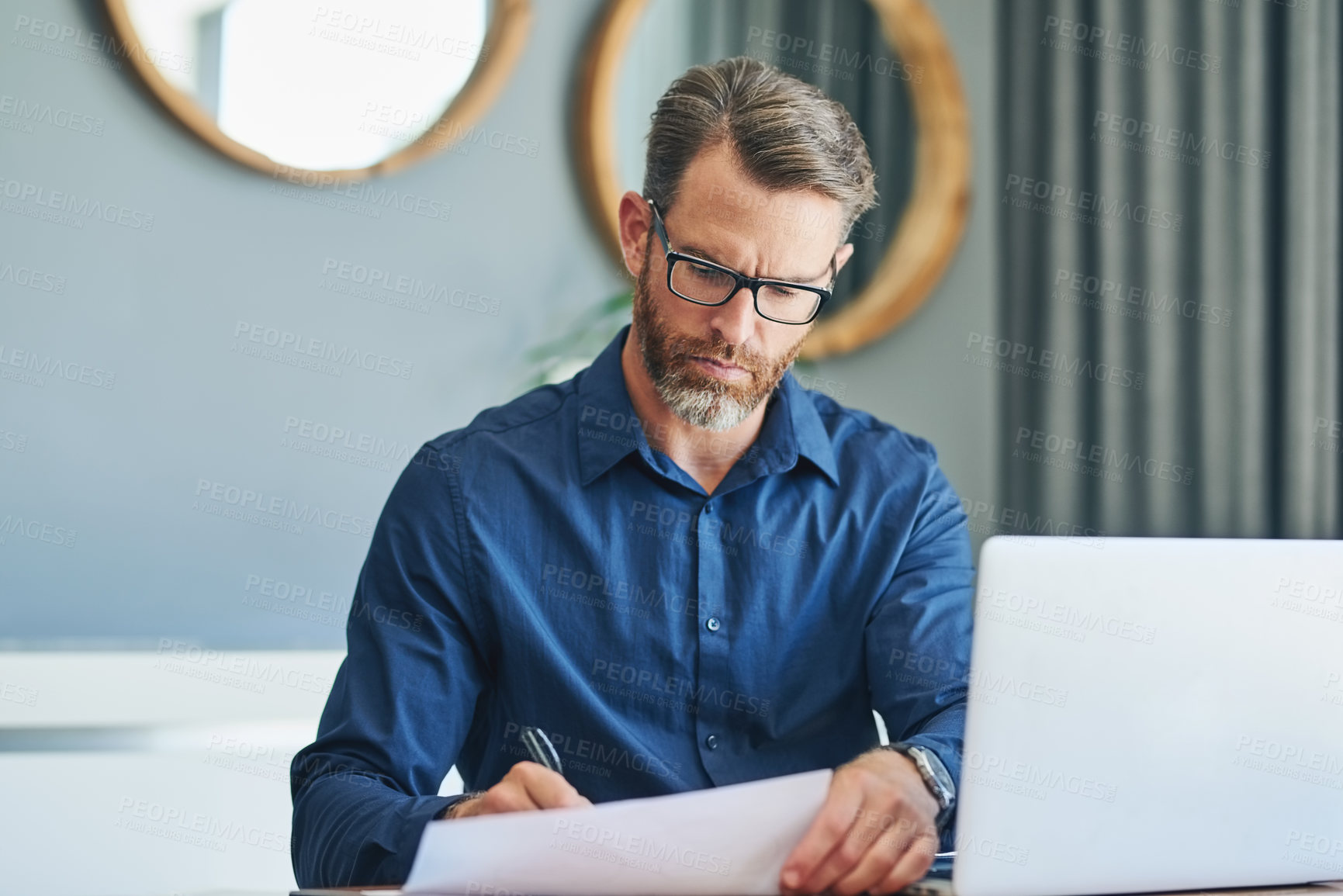 Buy stock photo Shot of a focussed middle aged businessman sorting out documents and working from home during the day