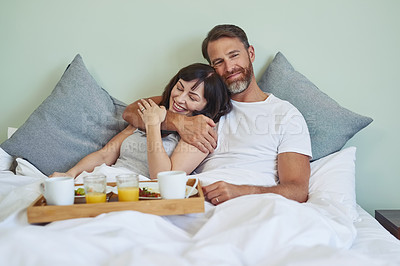 Buy stock photo Shot of a cheerful young couple sitting in bed while enjoying breakfast together during morning hours