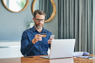 Buy stock photo Shot of a focussed middle aged businessman working on his laptop and paying bills with his credit card at home during the day