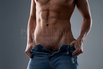 Buy stock photo Studio shot of an unrecognizable shirtless man undressing against a grey background