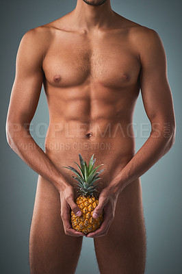 Buy stock photo Studio shot of an unrecognizable shirtless man posing with a pineapple against a grey background
