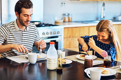 Buy stock photo Shot of a father and his little daughter having breakfast together at home