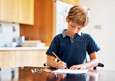 Buy stock photo Shot of a young boy doing his homework