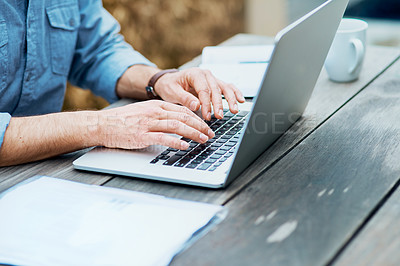Buy stock photo Closeup shot of an unrecognizable man using a laptop outdoors