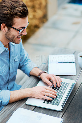 Buy stock photo Shot of a handsome young man using a laptop outdoors