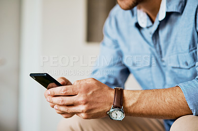 Buy stock photo Closeup shot of an unrecognizable man texting on a cellphone at home
