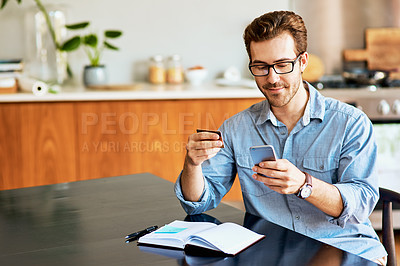Buy stock photo Shot of a handsome young man using a cellphone and credit card at home