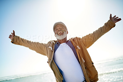 Buy stock photo Shot of a mature man standing with his arms outstretched at the beach