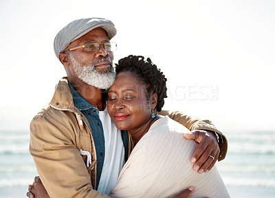 Buy stock photo Shot of a mature woman resting in her husband's arms at the beach