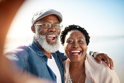 Buy stock photo Portrait of a mature couple taking selfies together at the beach