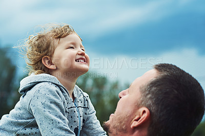 Buy stock photo Shot of a cheerful little girl being picked up by her father outside during a cloudy day